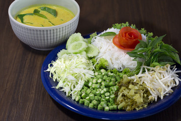 Thai rice noodle eaten with curry and veg. thai food (Thai language Kanom jeen) on blue dish and green bowl, All on brown wooden background