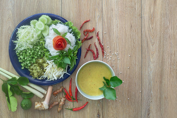 Thai rice noodle eaten with curry and veg. thai food (Thai language Kanom jeen) on blue dish and green bowl, All on brown wooden background .