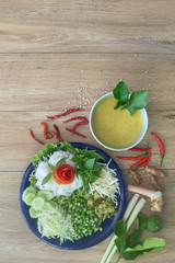 Thai rice noodle eaten with curry and veg. thai food (Thai language Kanom jeen) on blue dish and green bowl,