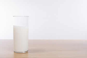 Glass with milk standing on table