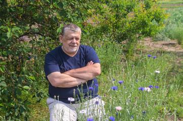 Outdoor portrait of senior Ukrainian peasant sitting in a spring garden and admiring Centaurea flowers
