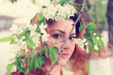 red hair women in apple flower branch
