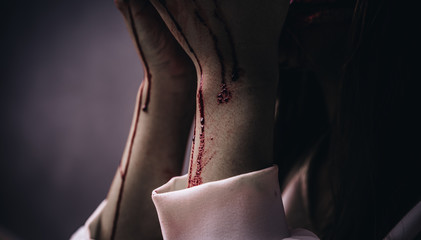 Closeup Zombie arm women death ghost with blood, darkness background, horror halloween festival concept