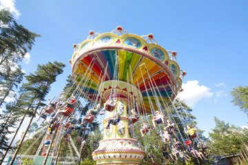 Colorful chain swing carousel in motion at amusement park on blue sky background.