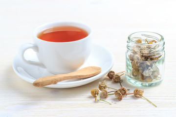 A cup of green tea with chamomile in a jar and a wooden spoon