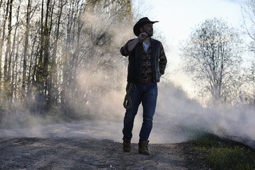 A cowboy in a thick smoke on the road