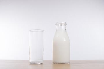 Tall glass alongside a bottle of milk