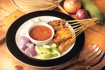 Asian food satay served with onion and cucumber