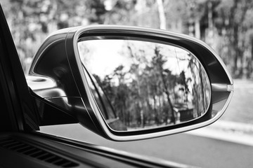 Сar mirror. Forest in rear view mirror closeup