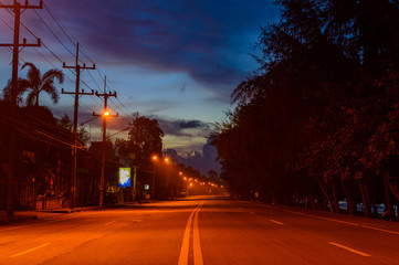 Empty street at early morning before dawn shrouded in mist illuminated by streets lights