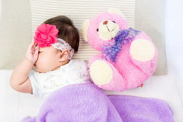 Portrait of sleeping baby  lying on a bed with head band and bear doll