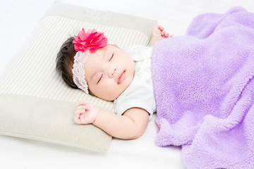 Portrait of sleeping baby  lying on a bed with head band