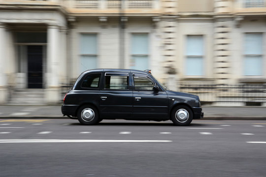 Panning shot of a black taxi in London.