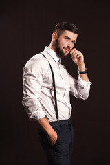 Young handsome muscular man with a beard, posing on a black background