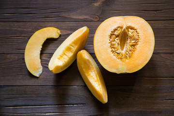 Half melon and slices on a dark wooden background