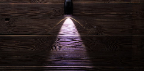 Included flashlight on wooden background