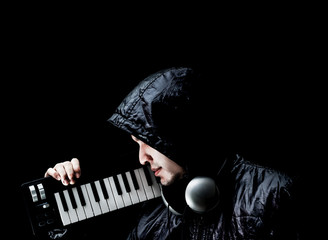asian male musician in black jacket posing on music keyboard synthesizer, isolated on black. music lover concept