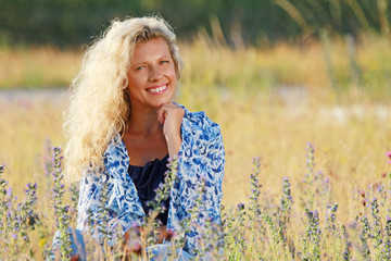 Happy mature woman relaxing in the meadow