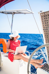 Woman freelancer on a sailboat with a laptop computer.