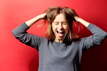Emotional stress. Frustrated caucasian young woman holding head in hands. Red background.