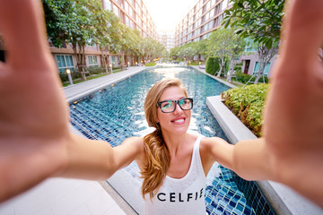 Youth and technology. Pretty young woman taking selfie on swiming pool background.