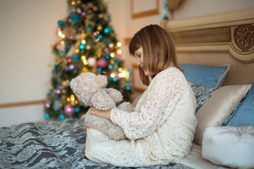 child girl in  dress with toy bear on  bed near  Christmas tree
