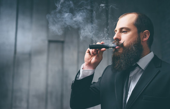 Elegant vaper. Handsome young bearded man in suit smoking vaporizer electronic cigarette.