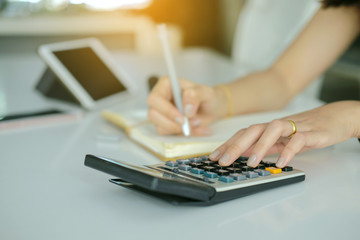 Woman hands working on calculator close up with blur  note book and tablet on tablework