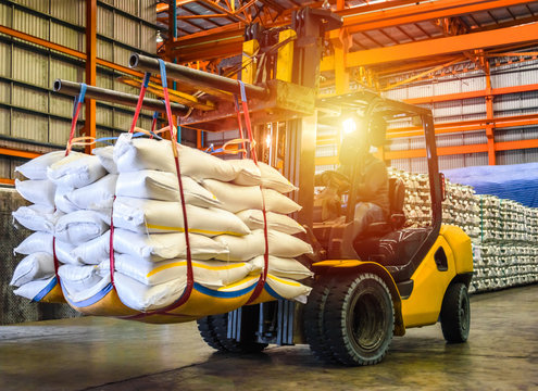Forklift handling sugar bag for stuffing into container for export,