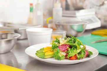 Plate with delicious salad on table