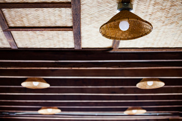 Close-up of neon light in bamboo chandelier on wood ceiling, handcraft from Thailand local style