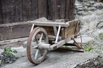 Ancienne brouette en bois devant une porte