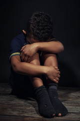 Little boy sitting on floor in darkness. Poverty concept