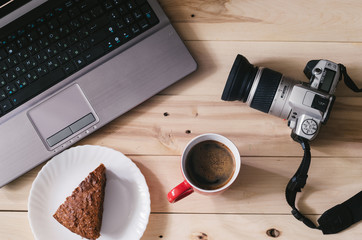 Camera and laptop on wooden background. Coffee and cake.