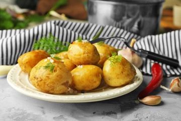 Plate with boiled potatoes on table