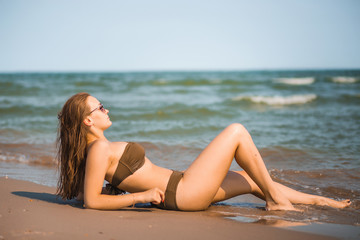 Sexy tanned girl in a bathing suit  lies on the seashore