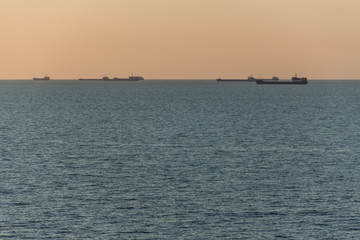 Trading ships or barges on the horizon of the sea during sunset or dawn.