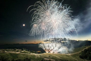 Fireworks on the top of the mountain in summer evening with moon in the sky