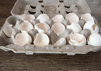Carton of Broken Egg Shells on wood plank board