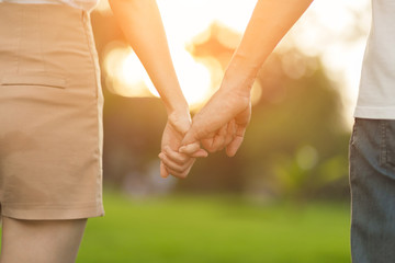 Lovers in the park tenderly hold hands together, blurred background.