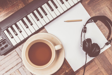 songwriter concept. piano, headphone, coffee cup, pencil & blank white paper on wooden floor