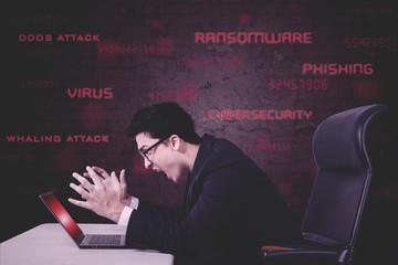 Stressful businessman screams on damaged laptop