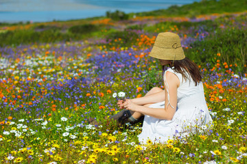 Young woman sitting in the sun in colourful wildflowers