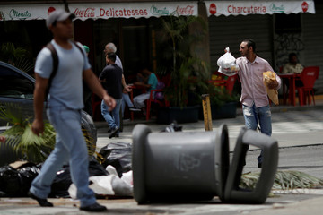 People walk through a barricade after a strike called to protest against Venezuelan President Nicolas Maduro's government in Caracas