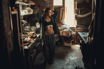 Girl worker in overalls and t-shirt stands in workshop among tools.