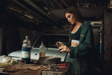 Girl worker in overalls and t-shirt stands in workshop among tools and lubricates  spare parts from car.