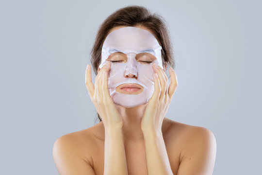 Woman with a cloth moisturizing mask on her face