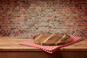 Wooden tray with checked tablecloth on table over brick wall background