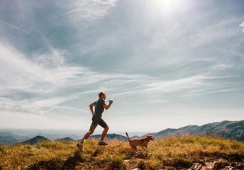 Man runs with his beagle dog on mountain top