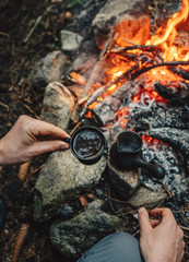 Man drinks hot coffee making on campfire